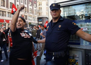 European strikes: A policeman stops a picketer as they demand for the closure of some shops