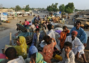 24 Hours: Pakistan flood survivors sit on a trucks