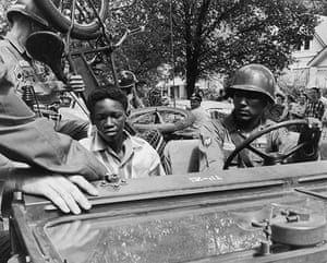Little Rock: National Guardsmen give a black student and his bicycle a lift to school