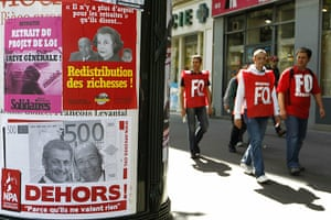 French Strike Update: French trade union members walk past anti goverment posters