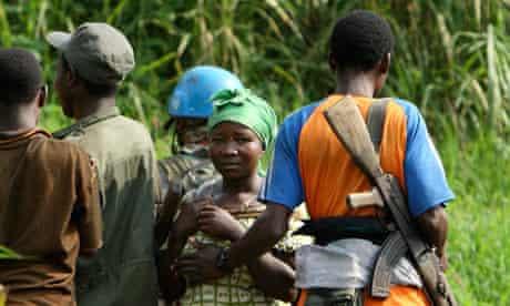 A Rwandan Hutu rebel gropes a woman as he passes her on a mountain path near Kimua in eastern Congo
