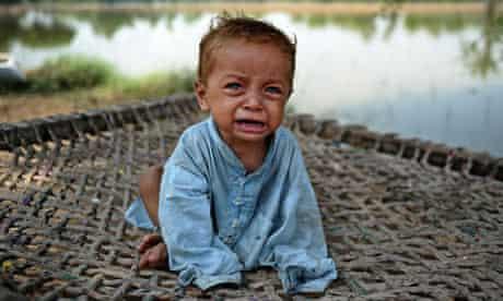 A Pakistani infant displaced by floods cries, Pakistan flooding