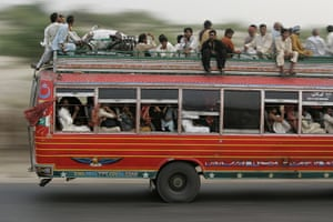 Pakistan Flooding Update: Pakistanis displaced by floods sit on top of a bus Pakistan flooding
