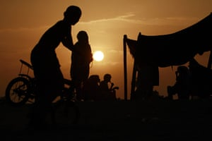 Pakistan Flooding Update: Pakistanis wait for relief goods as the sun sets at a camp