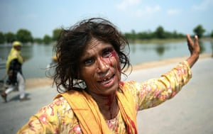 Pakistan Flooding Update: A Pakistani woman bleeds after being attacked for her aid ration