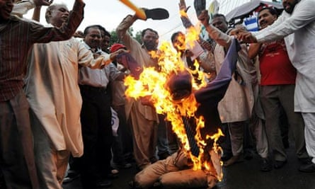 Pakistani Christians beat a burning effigy of Terry Jones because of his plans to burn the Qur'an