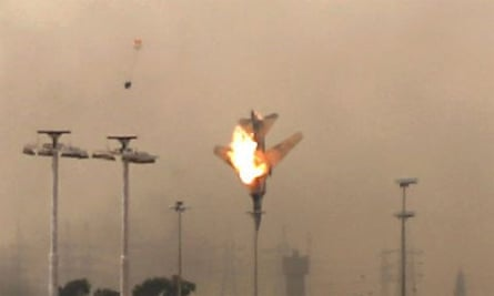 A burning jet plunges to the ground in Benghazi, Libya, with a pilot's ejection seat and parachute apparently visible in the background