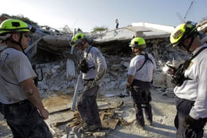 Haiti one year on: January 21: Rescuers tand outside a collapsed hospital