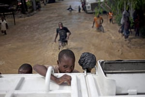 Haiti one year on: November 6: A boy holds on to a truck after hurricane Tomas