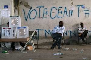 Haiti one year on: November 28:  Poll workers sit idle next to ballot boxes