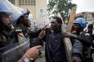 Haiti one year on: December 9: A young man argues with Nigerian members of Minustah
