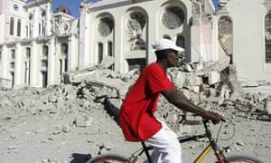 A man cycles past a damaged church in Port-au-Prince after the 2010 Haiti earthquake.