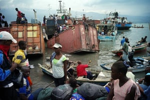 Haiti one year on: January 19: A Haitian family prepare to board a boat