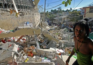 Haiti one year on: January 13: Haitians pass destroyed buildings in Port-au-Prince