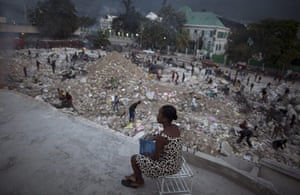Haiti one year on: September 30: A woman watches people scavenge for metal