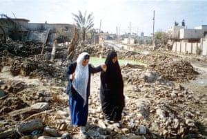 Gulf War: 1991: Women walk through rubble of bomb damage in Baghdad
