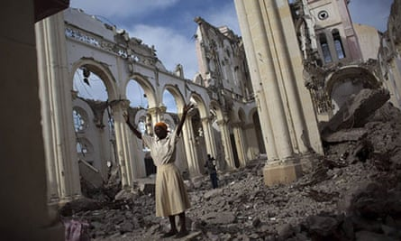 Woman prays in ruins of cathedral in Port-au-Prince, Haiti