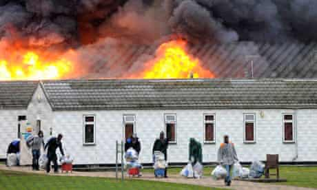 Inmates evacuate a burning building during the Ford prison riot.