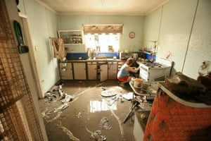 Brisbane Cleanup: A volunteer helps clean the kitchen of a property damaged by floodwaters