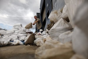 Brisbane Cleanup: A man removes sandbags from the entrance to a flood-damaged warehouse