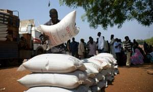 Sudanese men unload sacks of food