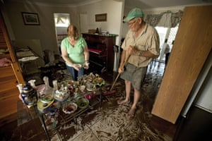 Brisbane Cleanup: Helen (L) and Trevor Goschnick mop up the aftermath of flood waters