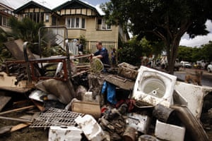 Brisbane Cleanup: A man adds to a pile of debris on the edge of a street