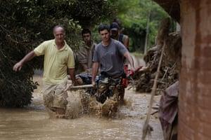 brazil mudslide aftermath: Residents carry a landslide victim in Teresopolis