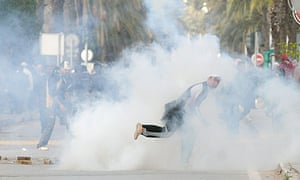 A Tunisian demonstrator throws a rock after police fired tear gas during demonstrations in Tunis