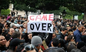 "A Tunisian demonstrator holds a placard reading ""Game Over"" during a rally at the interior ministry"