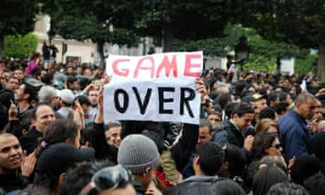 """A Tunisian demonstrator holds a placard reading """"Game Over"""" during a rally at the interior ministry"""