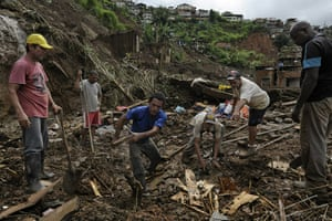 Brazil aftermath: Residents remove debris while searching for the bodies