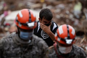 Brazil aftermath: Rescue workers try to recover the body of a landslide victim