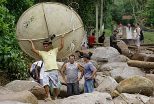 Brazil aftermath: A man carries a satellite dish recovered after a landslide in Campo Grande