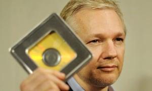 Julian Assange holds a CD containing data