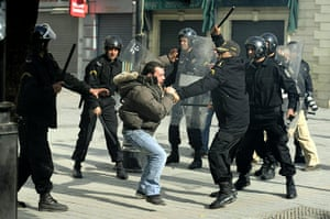 protests in tunisia: Police officers beat a demonstrator in Tunis