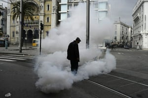 Tunis protest: A policeman stands in a cloud of teargas in Tunis