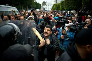 Tunis protest: A Tunisian protester holding a baguette talks to riot policemen