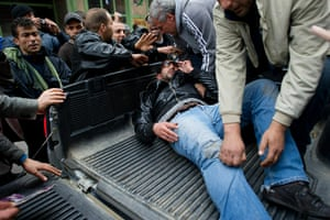 Tunis protest: A wounded Tunisian man is taken away by fellow protesters