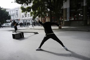 Tunis protest: A Tunisian protester prepares to throw a stone during a demonstration