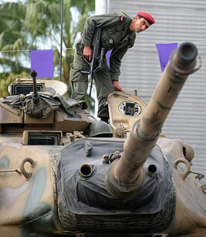Tunisia uprising: A Tunisian soldier stands guard on a tank facing demonstrators