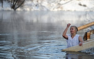 Orthodox epiphany: A woman makes a sign of the cross while standing Istra river