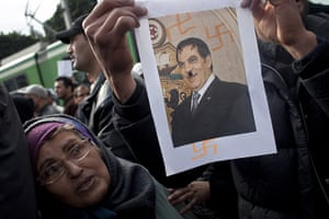 Tunisia uprising: A woman looks a picture of former President caricatured as Hitler