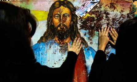 Egyptian Christians touch a blood-splattered mural inside the Coptic church in Alexandria