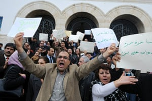 Tunisia update: Tunisian judges hold placards as they demonstrate in front of courthouse