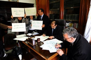 Tunisia update: Tunisian judges hold placards as they demonstrate inside Tunis' courthouse