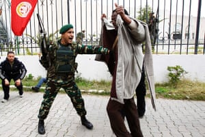 Tunisia protests: Protester ducks during gun fire at a demonstration in downtown Tunis