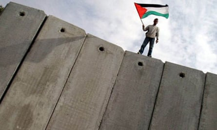 A Palestinian man stands on the Israeli barrier
