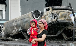 A Uighur woman and child walk past a charred car in Urumqi after riots exploded in July 2009