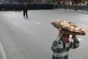egpyt protests: A boy carrying bread on his head runs away from a column of riot police